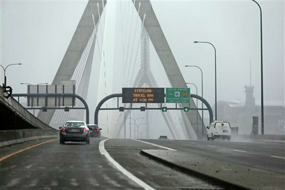 """Cars drive across the nearly empty Zakim Bridge prior to a mandatory statewide driving ban in Boston, Friday, Feb. 8, 2013. Mass. Gov. Deval Patrick declared a state of emergency Friday and banned travel on roads as of 4 p.m. as a blizzard that could bring nearly 3 feet of snow to the region began to intensify. As the storm gains strength, it will bring """"extremely dangerous conditions"""" with bands of snow dropping up to 2 to 3 inches per hour at the height of the blizzard, Patrick said. (AP Photo/Charles Krupa) / AP"""