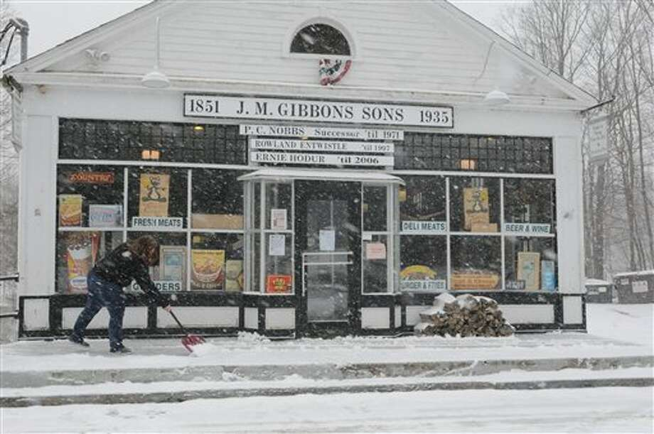 Granville Country Store employee Shawna Sperry clears snow from in front of the store to keep ahead of the approaching heavier snowfall later in the day Friday, Feb. 8, 2013. Snow began falling across the Northeast on Friday, ushering in what was predicted to be a huge, possibly historic blizzard and sending residents scurrying to stock up on food and gas up their cars. The storm could dump 1 to 3 feet of snow from New York City to Boston and beyond. (AP Photo/The Republican, Michael S. Gordon) / The Republican