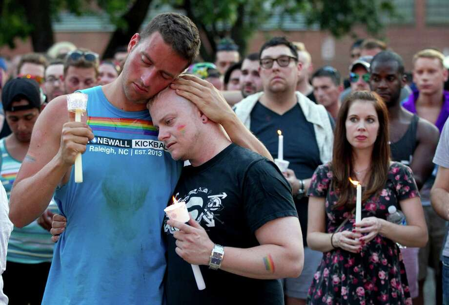 Ryan Gibson, left, embraces Tabor Winstead during a vigil for the victims of the Orlando shooting on Sunday, June 12, 2016 at the Legends Club on Hargett Street in downtown Raleigh, N.C.  The event was held by the LGBT community in Raleigh, after 50 people were killed in an Orlando nightclub.   (Robert Willett/The News & Observer via AP) Photo: Robert Willett, AP / The News & Observer