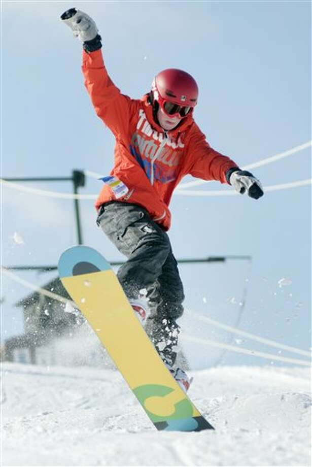Ben Colpean, 14, of Saginaw Township lands a jump while snowboarding on the snowboard terrain park at Apple Mountain in Freeland, Mich. on Friday, Feb. 8, 2013. Overnight snow caused all area schools to close for the day giving students the chance to spend a sunny winter's day snowboarding or skiing down the hill. (AP Photo/The Saginaw News, Jeff Schrier) / The Saginaw News/MLive.com