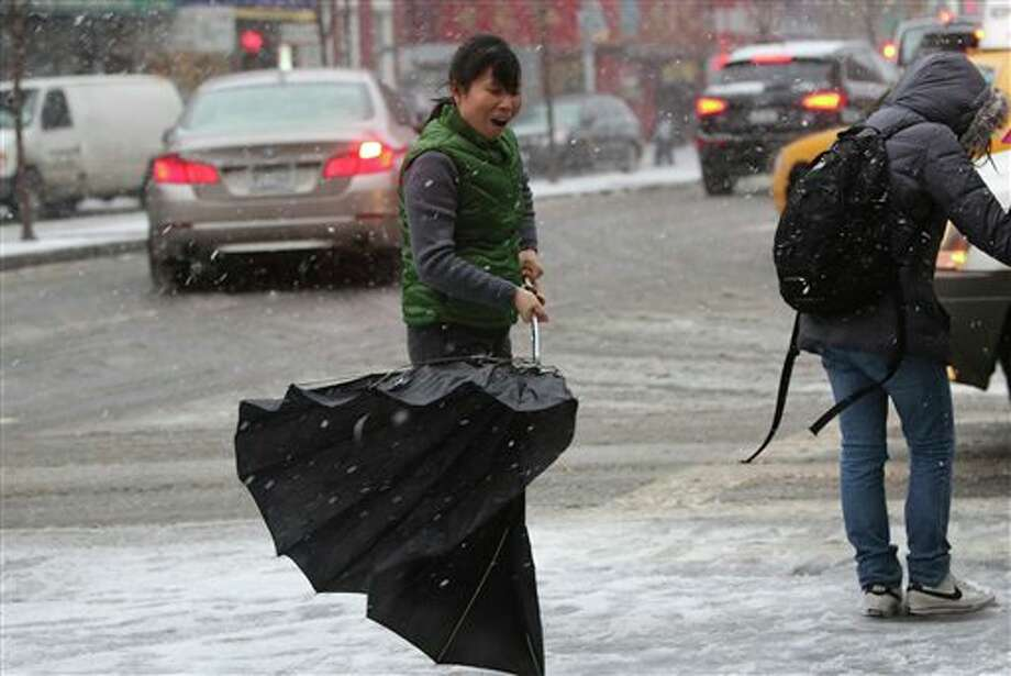 A woman's umbrella collapses in the wind while she waits at a crosswalk in New York's Chinatown, Friday, Feb. 8, 2013. Snow began to fall as a massive blizzard headed for the American Northeast on Friday, sending residents scurrying to stock up on food and supplies ahead of a storm poised to dump up to 3 feet of snow from New York City to Boston and beyond. (AP Photo/Mary Altaffer) / AP