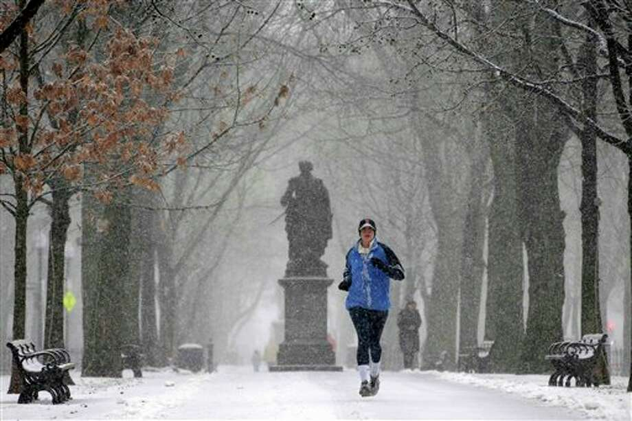 A runner runs in the snow in the park along Commonwealth Ave in Boston, Friday, Feb. 8, 2013. Snow began falling across the Northeast on Friday, ushering in what was predicted to be a huge, possibly historic blizzard and sending residents scurrying to stock up on food and gas up their cars. The storm could dump 1 to 3 feet of snow from New York City to Boston and beyond. (AP Photo/Gene J. Puskar) / AP2013