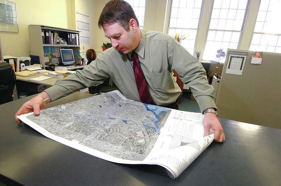 Hour photo / Alex von Kleydorff Town of Westport's Director of Planning and Zoning Laurence Bradley unfolds seven new FEMA flood maps for the town. / © 2012 The Hour Newspapers