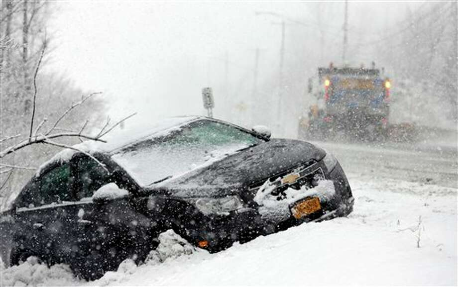 A plow truck passes a car stuck in a ditch during a winter snow storm in Buffalo, N.Y., Friday, Feb. 8, 2013. (AP Photo/David Duprey) / AP2013