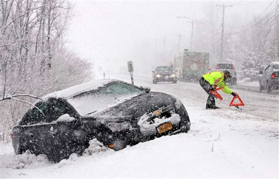 Tow truck operator Shawn Juhre sets up road safety reflectors before towing a car out of a ditch during a winter snow storm in Buffalo, N.Y., Friday, Feb. 8, 2013. Snow began falling across the Northeast on Friday, ushering in what was predicted to be a huge, possibly historic blizzard and sending residents scurrying to stock up on food and gas up their cars. The storm could dump 1 to 3 feet of snow from New York City to Boston and beyond. (AP Photo/David Duprey) / AP2013