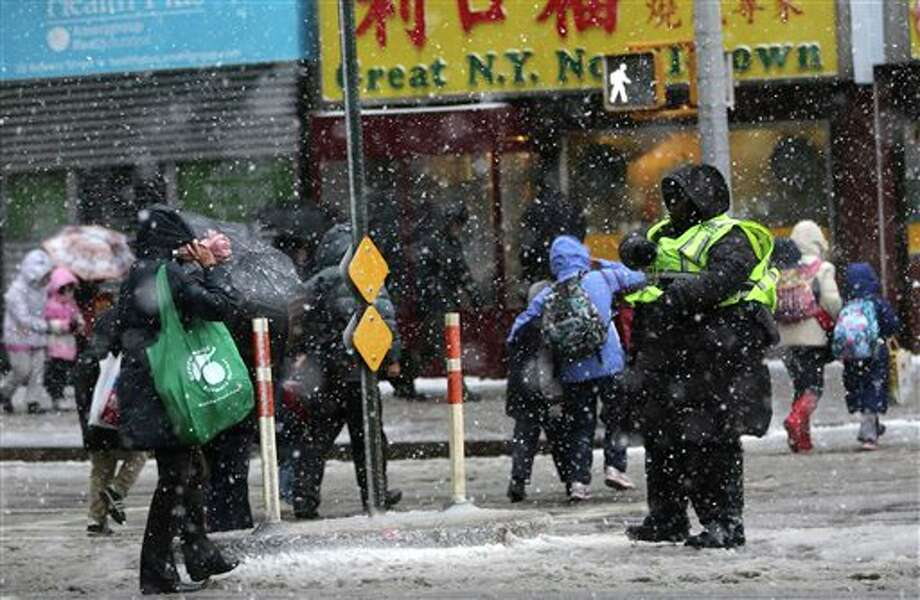 A crossing guard helps people get across the street in New York's Chinatown, Friday, Feb. 8, 2013. Snow began to fall as a massive blizzard headed for the American Northeast on Friday, sending residents scurrying to stock up on food and supplies ahead of a storm poised to dump up to 3 feet of snow from New York City to Boston and beyond. (AP Photo/Mary Altaffer) / AP
