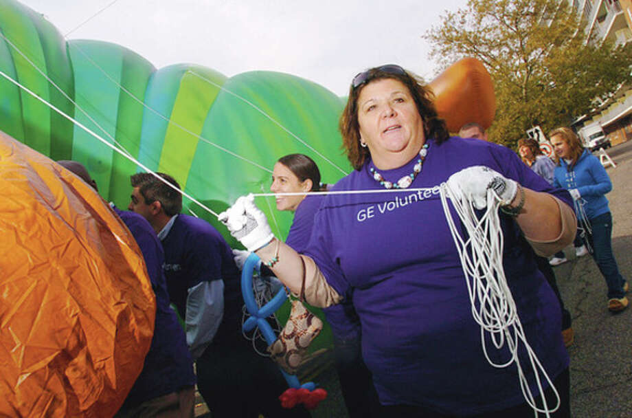 """Volunteer balloon handler, Danette Melchionne of GE, trains for the Thanksgiving parade during a press conference Thursday at Latham Park in Stamford. The volunteer balloon handlers, representatives from Stamford Downtown Special Services and Title Sponsor, UBS, gathered under the brand new 35-foot long """"The Very Hungry Caterpillar"""" balloon to announce details of the parade on Sunday the 20th. Hour photo / Erik Trautmann / (C)2011, The Hour Newspapers, all rights reserved"""