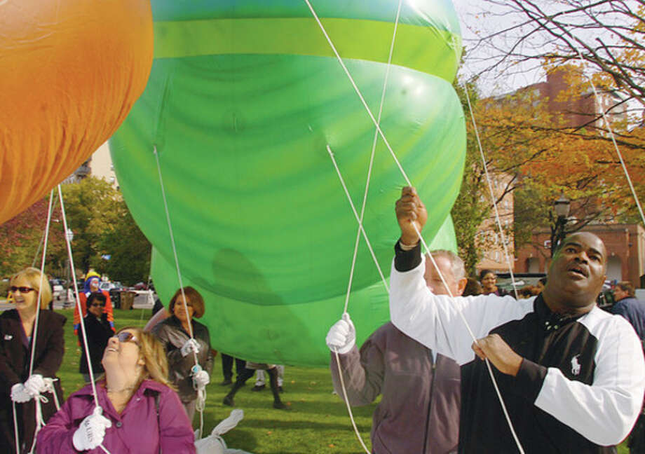 "Brian Epps of Big Events, leads the balloon handler training for the Thanksgiving parade during a press conference Thursday at Latham Park in Stamford. The volunteer balloon handlers, representatives from Stamford Downtown Special Services and Title Sponsor, UBS, gathered under the brand new 35-foot long ""The Very Hungry Caterpillar"" balloon to announce details of the parade on Sunday the 20th. Hour photo / Erik Trautmann / (C)2011, The Hour Newspapers, all rights reserved"