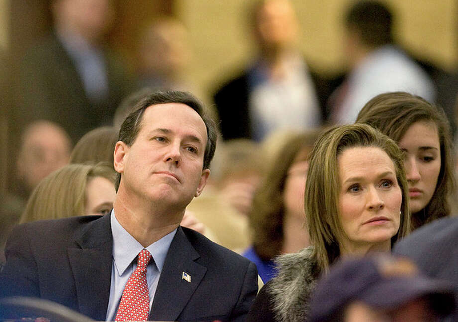 Republican presidential hopeful Rick Santorum listens to Rick Perry speak in the Faith & Freedom Coalition Prayer Breakfast at the Myrtle Beach Convention Center on Sunday, Jan. 15, 2012. (AP Photo/The Sun News, Janet Blackmon Morgan) / ©The Sun News 2011