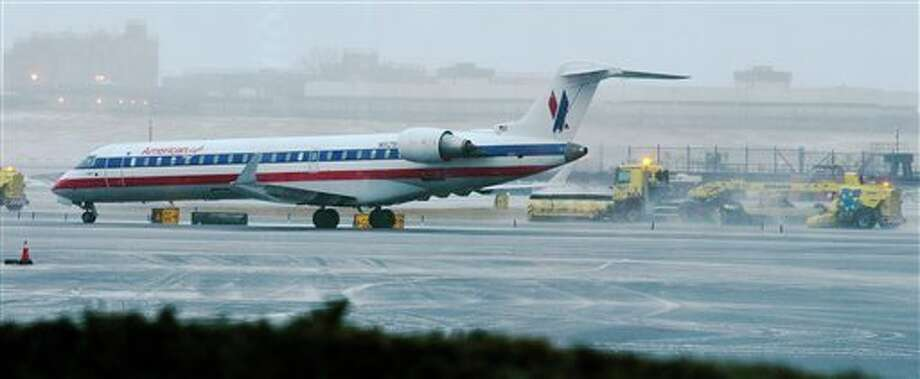 Grounds crews pass a plane as they clear the tarmac at LaGuardia Airport Friday, Feb. 8, 2013, in New York. A blizzard of potentially historic proportions threatens to strike the Northeast with 1 to 2 feet of snow forecast along the densely populated Interstate 95 corridor from New York City to Boston and beyond. (AP Photo/Frank Franklin II) / AP2013