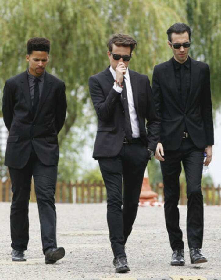 Radio dj Nick Grimshaw, centre, and two other mourners leave Edgwarebury Cemetery, in London, Tuesday July 26, 2011, after attending the funeral of singer Amy Winehouse. The soul diva, who had battled alcohol and drug addiction, was found dead Saturday at her London home. She was 27. (AP Photo/Kirsty Wigglesworth)