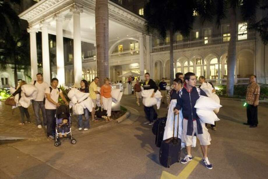 Hotel guests from the Moana Surfrider evacuate early Friday, March 11, 2011 in Honolulu. The state of Hawaii is under a tsunami warning due to a large 8.9 earthquake which struck off Japan. The earthquake is believed to have generated a tsunami wave. The Pacific Tsunami Center expects the wave to hit Oahu at 3:21 a.m. Hawaiian Standard Time. (AP Photo/Eugene Tanner)