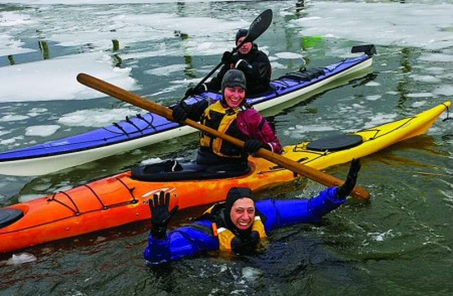 Experienced cold weather kayakers Bonnie Aldinger and Tom Klinger help novice Larry Wilner during the Cold Water Survival training in Long Island Sound at a workshop at the Small Boat Shop Saturday. Hour photo / Erik Trautmann