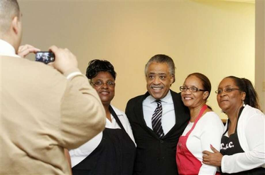 The Rev. Al Sharpton poses for a photo with church members, Delores Meeks, left, Loretta Murphy, right, and Elaine King, second from right, following a news conference at Mount Carmel Baptist Church in Waterloo, Iowa on Monday, May 23, 2011. Sharpton is opening an Iowa Chapter of his National Action Network in Waterloo. (AP Photo/Waterloo Courier, Dawn J. Saget)