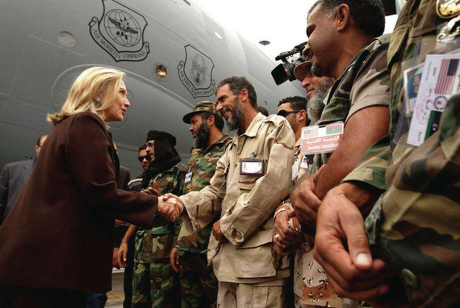 U.S. Secretary of State Hillary Rodham Clinton meets Libyan soldiers at the steps of her C-17 military transport upon her arrival in Tripoli in Libya, Tuesday Oct. 18, 2011. The Obama administration on Tuesday increased U.S. support for Libya's new leaders as Secretary of State Hillary Rodham Clinton made an unannounced visit to Tripoli and pledged millions of dollars in new aid, including medical care for wounded fighters and additional assistance to secure weaponry that many fear could fall into the hands of terrorists. (AP Photo/Kevin Lamarque, Pool) / Copyright 2011 The Associated Press. All rights reserved. This material may not be published, broadcast, rewritten or redistributed.