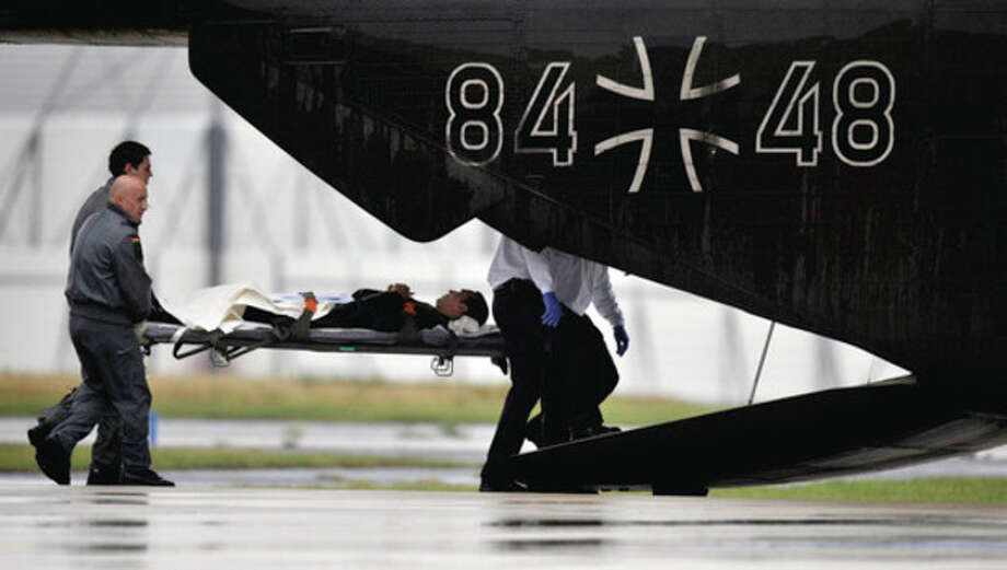 German army soldiers carry an injured victim from Libya to a helicopter at the military part of the Cologne airport, Tuesday, Oct. 18, 2011. A plane with 39 victims of Libya arrived in Cologne Tuesday afternoon to receive medical treatment in various German hospitals. (AP Photo/dapd, Sascha Schuermann) / dapd