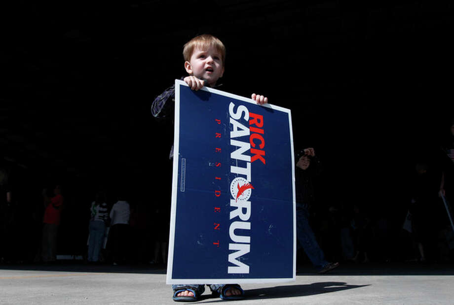 Jameson Williams, 2, of Sarasota, holds a sign outside a scheduled campaign event for Republican presidential candidate, former Pennsylvania Sen. Rick Santorum, at Sarasota Bradenton International Airport in Sarasota, Fla., Sunday, Jan. 29, 2012. Santorum is staying home in Philadelphia to be with his 3-year-old hospitalized daughter Isabella, and is canceling campaign stops in Florida. (AP Photo/Paul Sancya) / AP
