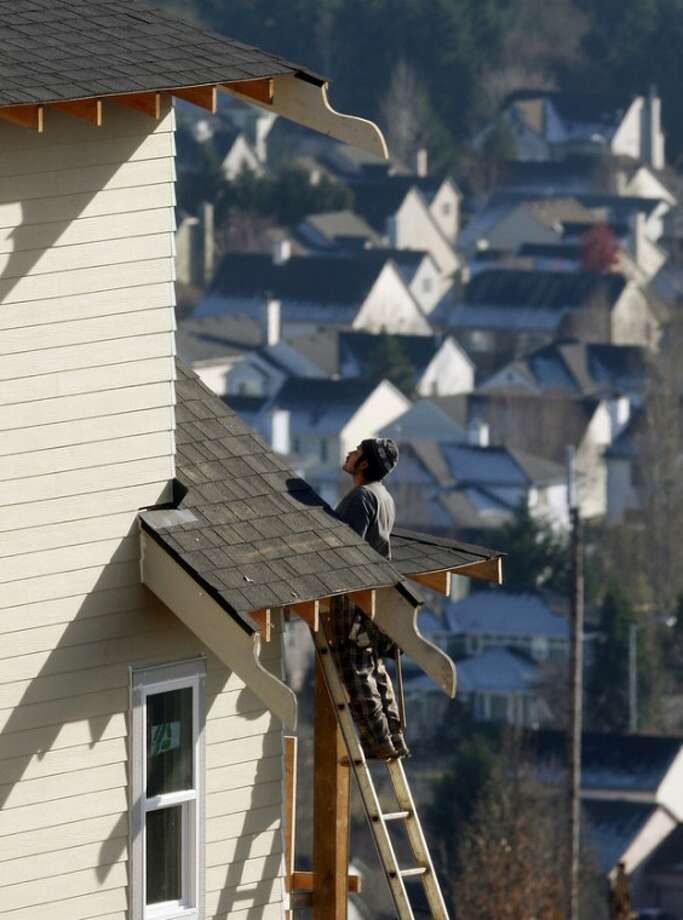 In this Dec. 20, 2011 photo, a carpenter works on a roof of a home in Happy Valley, Ore. U.S. home prices fell in most major cities for the second straight month, further evidence that the housing recovery will be bumpy. (AP Photo/Rick Bowmer)