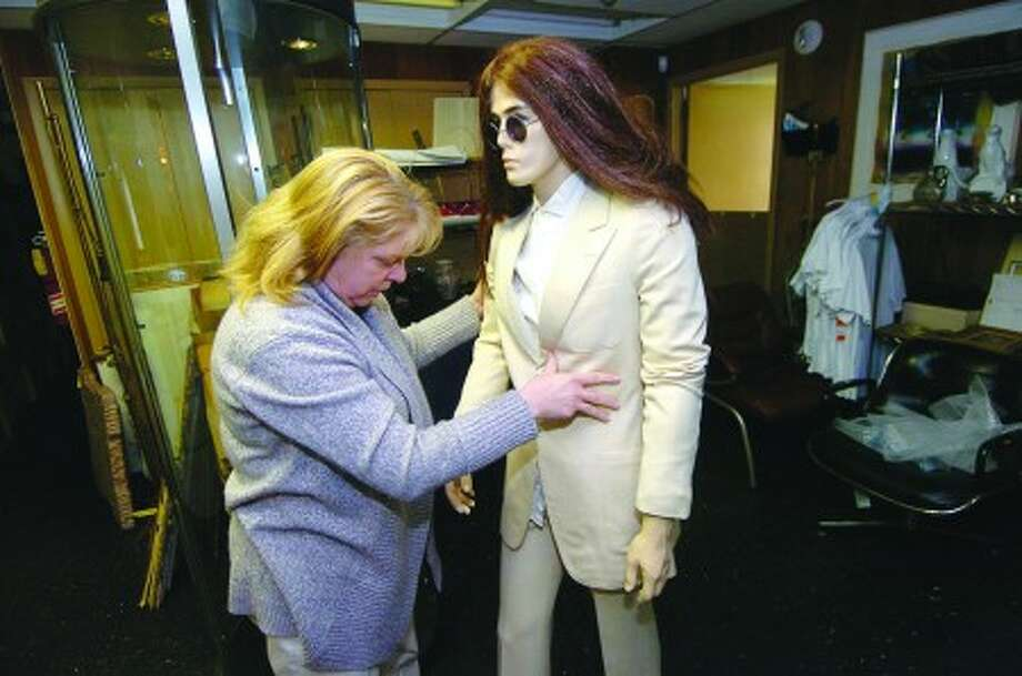 Photo/Alex von Kleydorff. Kathy Braswell moves a mannequin out of the case with the John Lennon Abbey Road white suit which sold at auction over the weekend