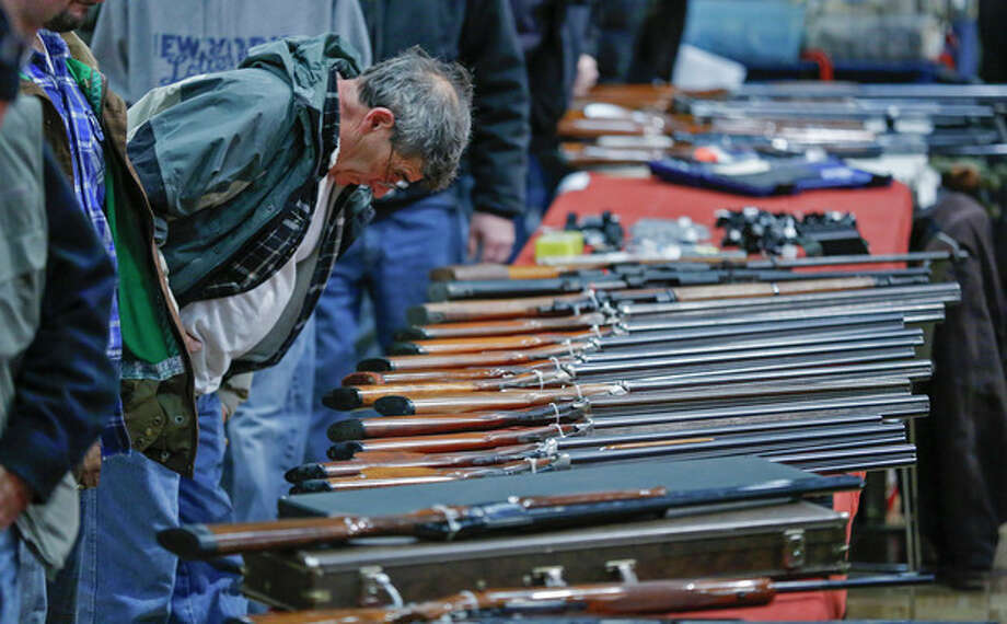"""FILE - In this Jan. 26, 2013 file photo, a customer looks over shotguns on display at the annual New York State Arms Collectors Association Albany Gun Show at the Empire State Plaza Convention Center in Albany, N.Y. A bipartisan quartet of senators, including two National Rifle Association members and two with """"F"""" ratings from the potent firearms lobby, are quietly trying to reach compromise on expanding the requirement for gun-sale background checks. (AP Photo/Philip Kamrass, File) / FR170784 AP"""