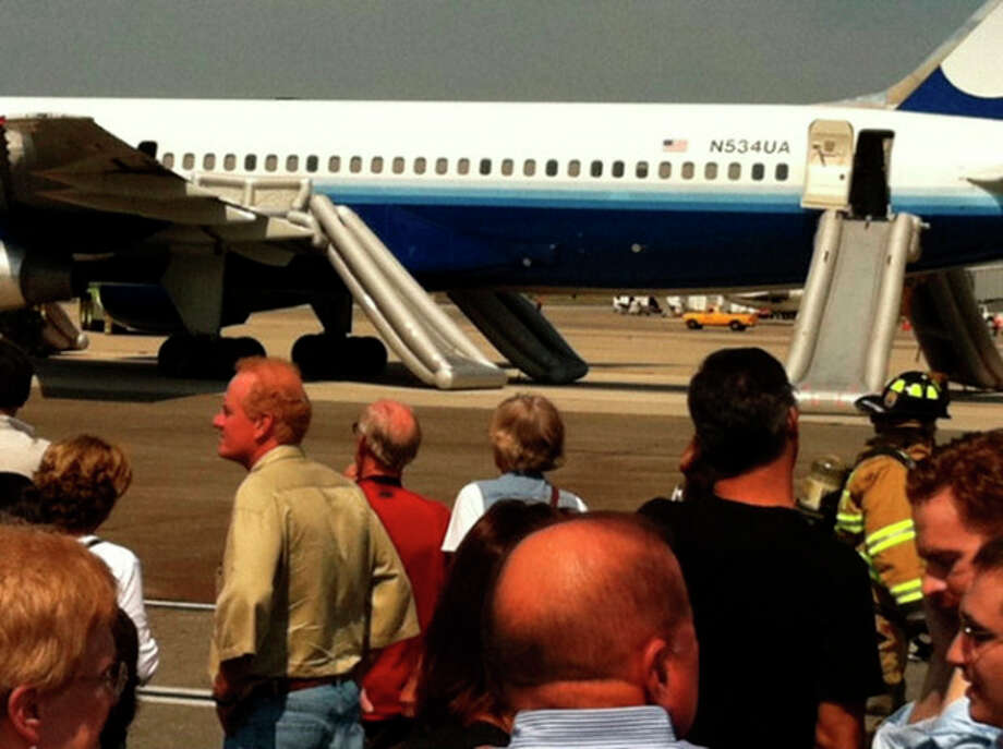 In this photo provided by Jodi Gersh, passengers evacuated via emergency chutes from a United Airlines plane bound for San Francisco stand on the tarmac after the plane experienced engine trouble and was forced to land at Dulles International Airport in Chantilly, Va. Wednesday, Sept. 14, 2011. U.S. Supreme Court Justice Ruth Bader Ginsburg, who is 78 and has battled cancer, was aboard the flight and was also forced to slide down an emergency chute, a court spokeswoman said. (AP Photo/Jodi Gersh) / Jodi Gersh