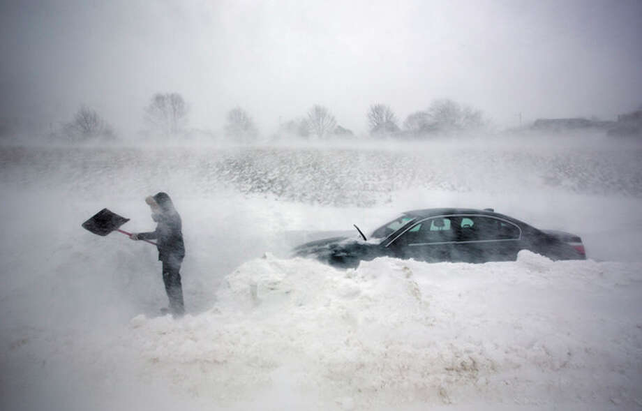 A woman digs out her car after it was blocked in by drifting snow during a blizzard, Saturday, Feb. 9, 2013, in Portland, Maine. The storm dumped more than 30 inches of snow as of Saturday afternoon, breaking the record for the biggest storm on record. (AP Photo/Robert F. Bukaty) / AP