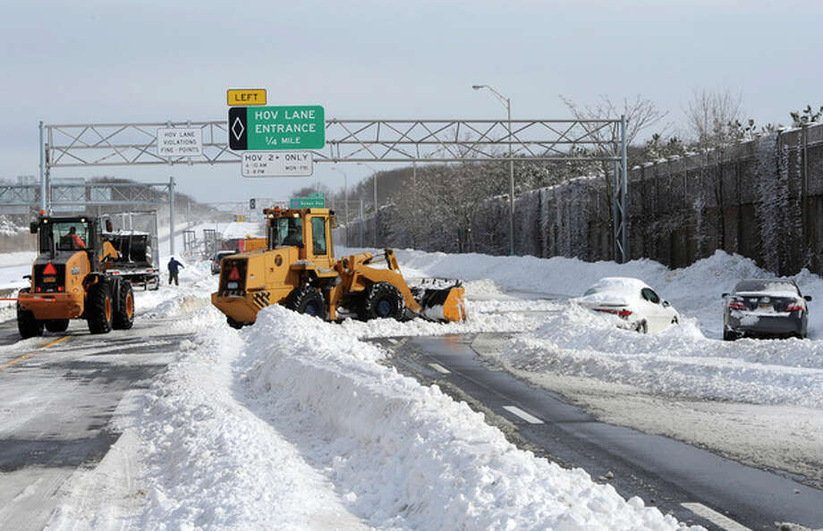Payloaders clear snow from the Long Island Expressway just west of exit 59 Ocean Ave where several cars are abandoned after a snow storm on Saturday, Feb. 9, 31, 2013, in Ronkonkoma , N.Y. (AP Photo/Kathy Kmonicek) / FR170189 AP