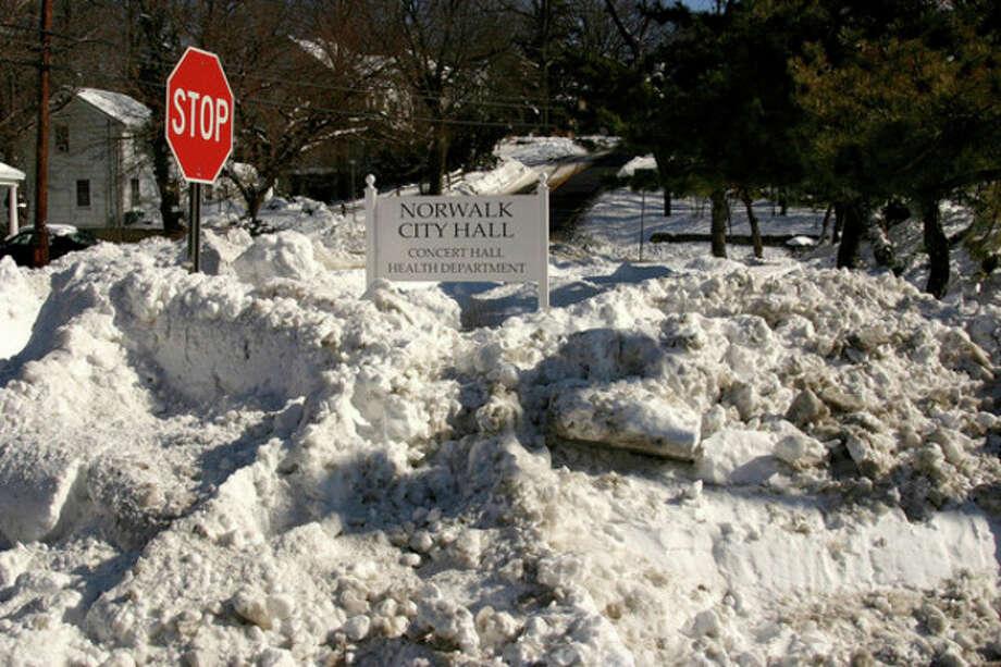 Hour photo / Chris BosakSnow is piled high at Norwalk City Hall on Sunday.