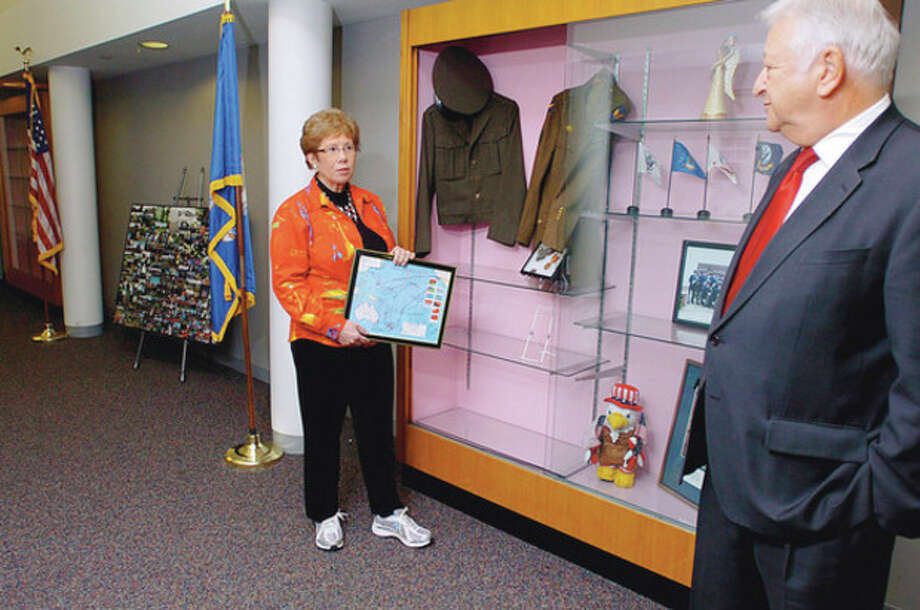 Hour photo / Erik Trautmann As Mayor Richard Moccia looks on, Norwalk Registar of Voters, Karen Doyle Lyons, sets up display cabinets outside her office in City Hall with loaned military memorabilia. / (C)2011, The Hour Newspapers, all rights reserved