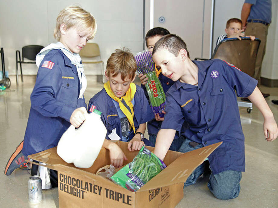 Photo by Danielle Robinson From left, Cub Scout Pack 17 members Aidan Jasinski, 5, Alex Jelilian, 8, Everet Lee, 8, and Ryan Witty, 8, assemble one of 12 Thanksgiving dinner boxes for Wilton families in need at the Comstock Community Center on Sunday afternoon.