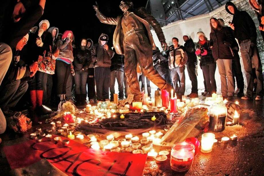 Candles and memorabilia are placed by well wishers at the foot of a statue of Joe Paterno outside Beaver Stadium on the Penn State University campus Saturday, Jan. 21, 2012. (AP Photo/Gene J. Puskar) / AP2012