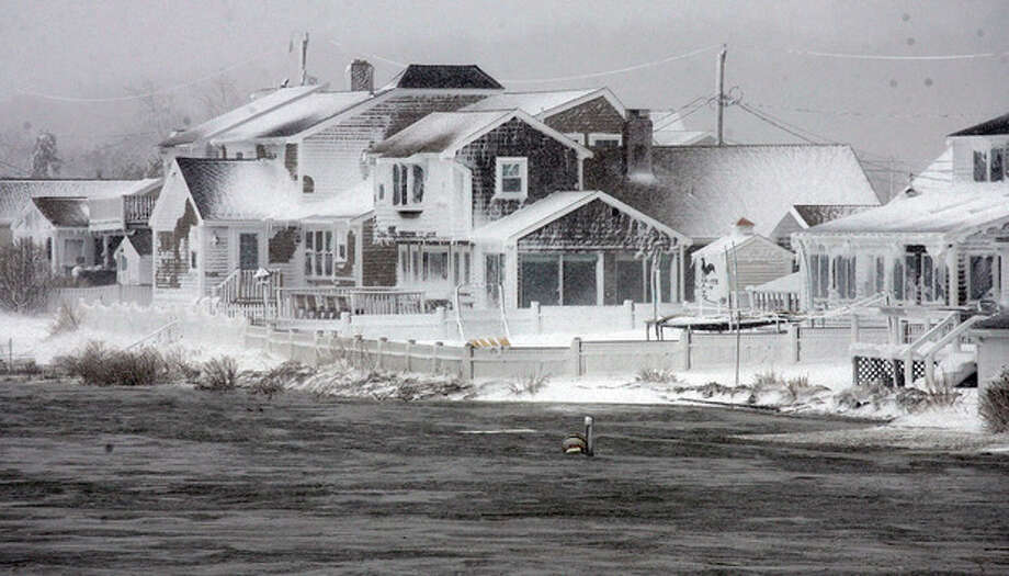 Wet snow coats houses along the South River at high tide in the Humarock coastal neighborhood of Scituate Mass. on Saturday, Feb. 9, 2013. A behemoth storm packing hurricane-force wind gusts and blizzard conditions swept through the Northeast overnight. (AP Photo/The Patriot Ledger, Greg Derr) / The Patriot Ledger