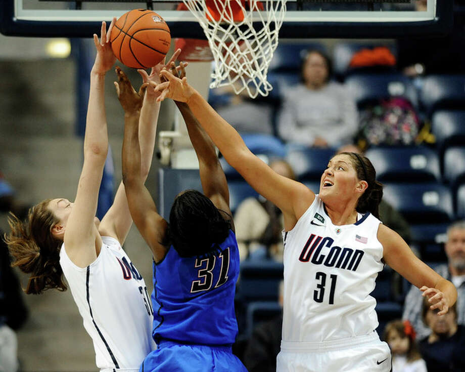 Connecticut's Breanna Stewart, left blocks a shot attempt by DePaul's Jasmine Penny, center, as Connecticut's Stefanie Dolson, right, defends during the first half of an NCAA college basketball game in Storrs, Conn., Sunday, Feb. 10, 2013. (AP Photo/Jessica Hill) / FR125654 AP