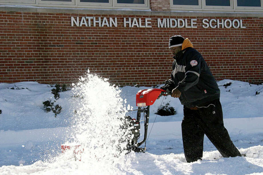 Hour photo / Chris BosakNorwalk Board of Education employee Ronald Spencer clears the sidewalks in front of Nathan Hale Middle School on Sunday.