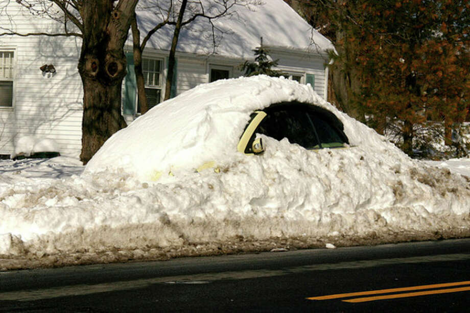 Hour photo / Chris BosakA car is buried under snow on Strawberry Hill Avenue in Norwalk on Sunday.
