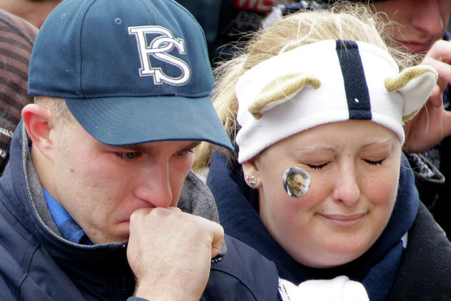Molly Johnson, right, a Penn State student from Wilmington, Del., and fellow student, senior Ian Kenney pay their respects at a statue of Joe Paterno outside Beaver Stadium on the Penn State University campus after learning of Paterno's death on Sunday, Jan. 22, 2012, in State College,Pa. (AP Photo/Gene J. Puskar) / AP2012