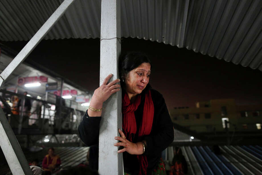 An Indian woman weeps as she watches from a staircase as rescue workers tend to the bodies of those killed in a stampede on a railway platform at the main railway station in Allahabad, India, Sunday, Feb. 10, 2013. At least ten Hindu pilgrims attending the Kumbh Mela were killed and more then thirty were injured in a stampede on an overcrowded staircase, according to Railway Ministry sources. (AP Photo/Kevin Frayer) / AP