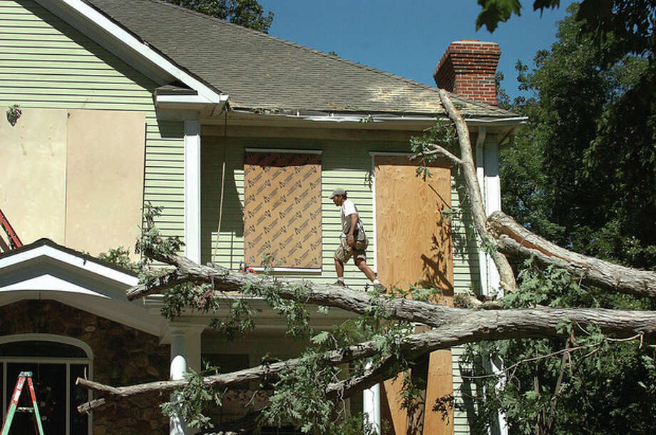 Hour photo/ Alex von Kleydorff Tree crews work to remove piece by piece a tree that landed on a house and car off Borglum Road in Wilton Monday. / 2011 The Hour Newspapers