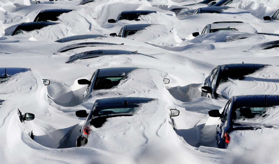Snow begins to melt on cars parked at a dealership after a winter storm in Hartford, Conn., Sunday, Feb. 10, 2013. A howling storm across the Northeast left much of the New York-to-Boston corridor covered with more than three feet of snow on Friday into Saturday morning. (AP Photo/Jessica Hill) / FR125654 AP
