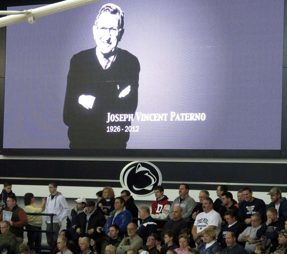 A video board at Penn State's Rec Hall displays an image of former football coach Joe Paterno during a moment of silence before a college wrestling meet between Iowa and Penn State on Sunday, Jan. 22, 2012. Paterno, a sainted figure at Penn State for almost half a century but scarred forever by the child sex abuse scandal that led to his stunning dismissal, died Sunday at age 85. (AP Photo/Genaro C. Armas) / AP
