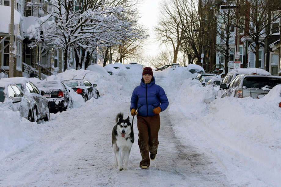 Jennifer Renz and her dog Gus run down East Third street in the South Boston neighborhood of Boston early Sunday morning, Feb. 10, 2013 in Boston. (AP Photo/Gene J. Puskar) / AP