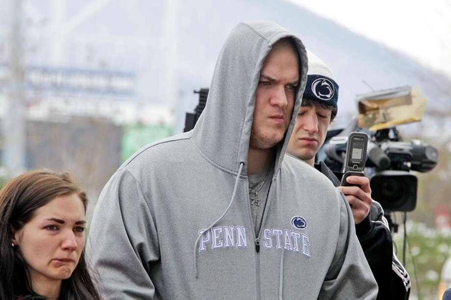 Penn State football player Eric Shrive, center, from Scranton, Pa., pays his respects at a statue of Joe Paterno outside Beaver Stadium on the Penn State University campus after learning of Paterno's death on Sunday, Jan. 22, 2012, in State College,Pa. (AP Photo/Gene J. Puskar) / AP