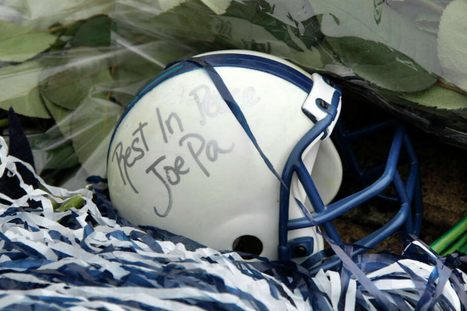 A miniature football helmet lies among flowers left at the foot of a statue of Joe Paterno outside Beaver Stadium on the Penn State University campus after learning of his death Sunday, Jan. 22, 2012 in State College,Pa.. (AP Photo/Gene J. Puskar) / AP