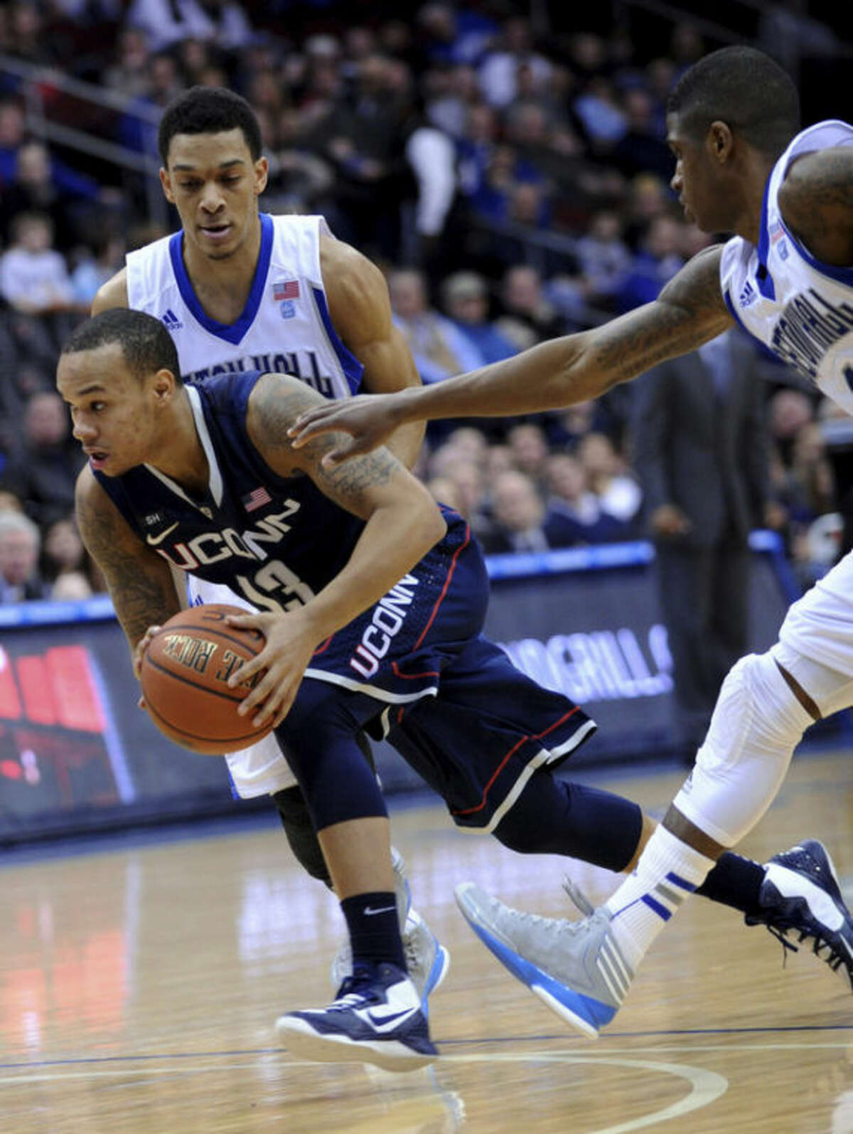 Connecticut's Shabazz Napier (13) drives to the basket between Seton Hall's Tom Maayan and Aaron Cosby, right, during the first half of an NCAA college basketball game Sunday, Feb. 10, 2013, in Newark, N.J. Connecticut won 78-67. (AP Photo/Bill Kostroun)