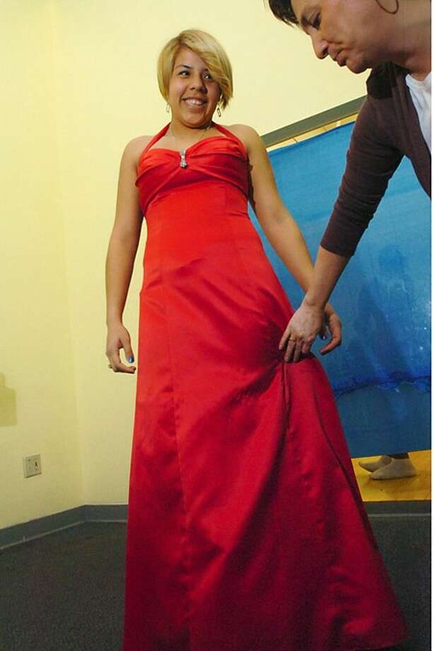 Norwalk High School senior Kristin Medina tries on prom dresses at the Christian Community Action 3rd annual Prom Dress Extravaganza with the help of volunteer Penny Spinola at the Norwalk Y Saturday. Hour photo / Erik Trautmann