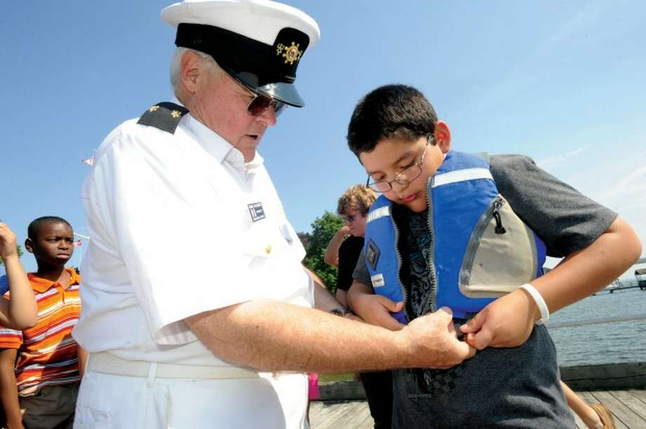 Education Officer George Hallenbeck gets Young Mariner Deivis Castro ready for his boat trip where the 5th grade low income students graduated from the scholorship program at the Stamford Yacht Club Tuesday. photo/matthew vinci