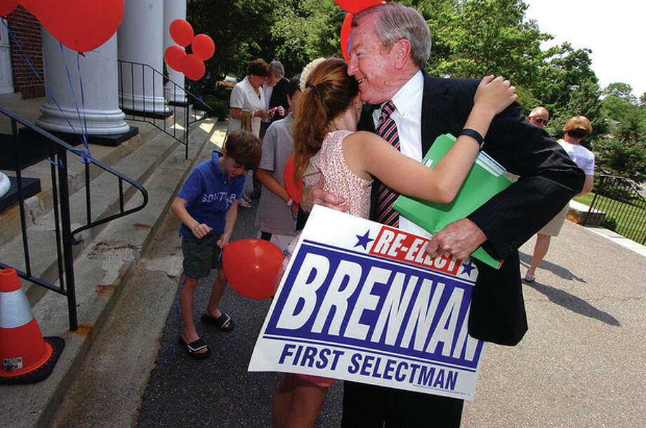 Photo by Alex von Kleydorff. Bill Brennan is all smiles as he gets a hug from granddaughter Amelia MacGregor, 11, while surrounded by family and supporters after he announced his re-election bid for First Selectman Tuesday in front of Wilton Town Hall. / 2011 The Hour Newspapers