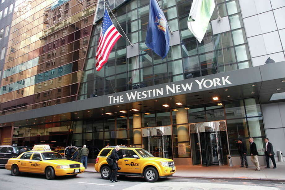A man hails a taxi in front of the Westin New York hotel, Wednesday, Feb. 1, 2012 in New York. Starwood Hotels & Resorts Worldwide Inc. said Thursady, Feb. 2, its fourth-quarter net income dropped 51 percent on impairment charges and other items, but its performance beat analysts' expectations. (AP Photo/Mark Lennihan) / AP