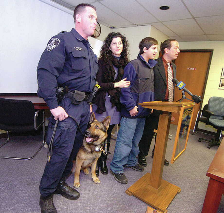 Hour photo/ Alex von Kleydorff Stamford K9 Police officer Seth O'Brien with Cooper and 13-year-old Teddy Murantz with mother, Marni, and dad, David. / ©2012 The Hour Newspapers