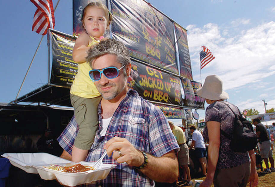 Hour photo / Erik Trautmann Matt Bergin sports a passenger as he digs into barbeque at the 2011 Norwalk Seaport Association Oyster Festival Saturday at Veterans Memorial Park. / (C)2011, The Hour Newspapers, all rights reserved